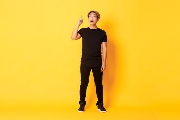 Longitud total de hombre asiático guapo pensativo, levantando el dedo, tiene una buena idea, pared amarilla de pie