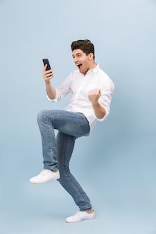 Longitud total de un joven apuesto alegre que se encuentran aisladas en azul, sosteniendo el teléfono móvil, celebrando