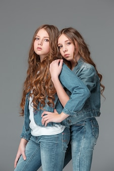 Longitud total de joven delgada femenina en jeans de mezclilla sobre fondo gris