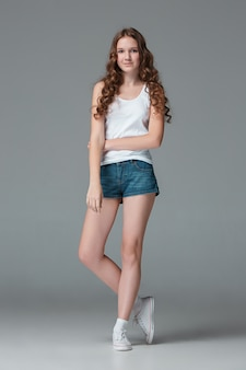 Longitud total de joven delgada mujer en pantalones cortos de mezclilla en la pared gris