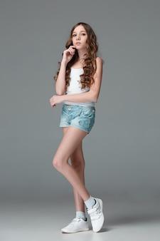 Longitud total de joven delgada mujer en pantalones cortos de mezclilla sobre fondo gris