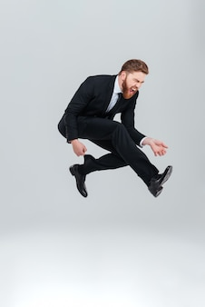 Longitud total joven hombre de negocios tan feliz en traje negro saltando en estudio. fondo gris aislado