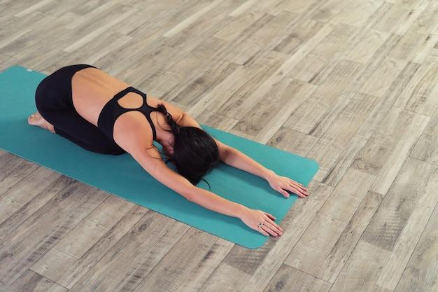 Longitud total de una joven mujer sentada en pose de niño sobre una estera de yoga