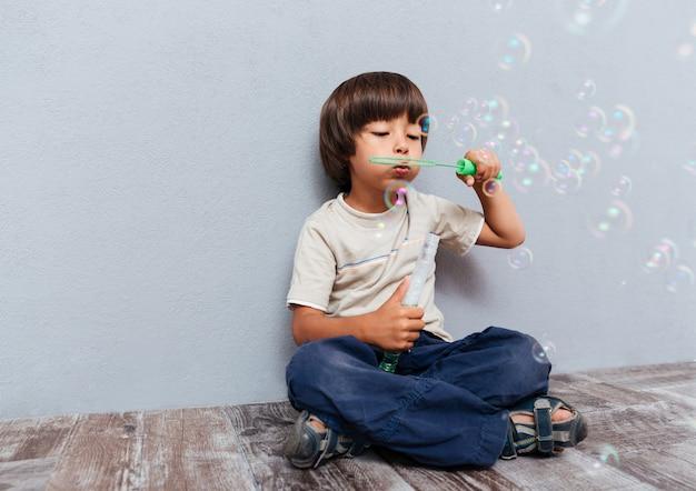 Longitud total de lindo niño sentado y soplando pompas de jabón