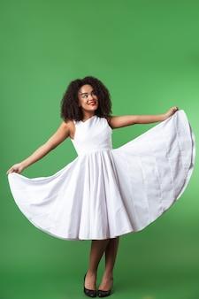 Longitud total de una mujer africana feliz vistiendo un vestido celebrando aislado, posando