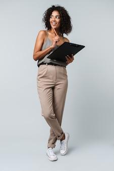 Longitud total de una mujer africana sonriente que se encuentran aisladas, sosteniendo el bloc de notas y el lápiz