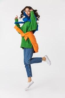 Longitud total de mujer alegre en ropa colorida sonriendo y saltando, aislado en blanco