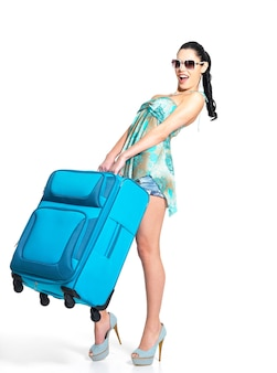 Longitud total de mujer casual sostiene la pesada maleta de viaje