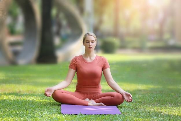 Longitud total de mujer haciendo ejercicio en la estera en el parque
