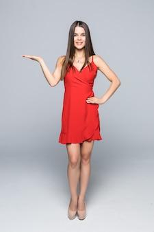 Longitud total de mujer joven feliz mostrando un producto - espacio de copia vacío en la palma de la mano abierta, sobre pared blanca