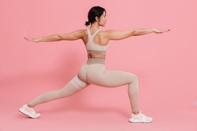 Longitud total de una mujer joven en forma saludable vistiendo ropa deportiva haciendo ejercicios de estiramiento aislado sobre pared rosa