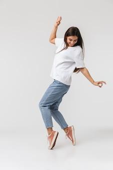 Longitud total de una mujer joven sonriente casualy vestida saltando aislado en blanco