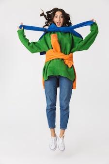 Longitud total de mujer optimista en ropa colorida sonriendo y saltando, aislado en blanco