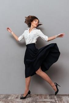 Longitud total de mujer en ropa de negocios corriendo en estudio y mirando hacia atrás en gris