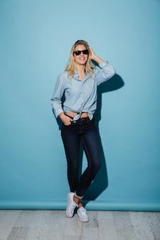Longitud total mujer sonriente en camisa y gafas de sol