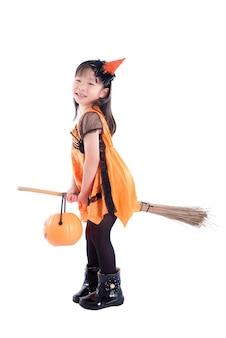 Longitud total de niña vestida con traje de halloween escoba sobre fondo blanco