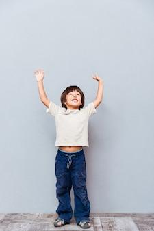 Longitud total de niño alegre de pie con las manos levantadas