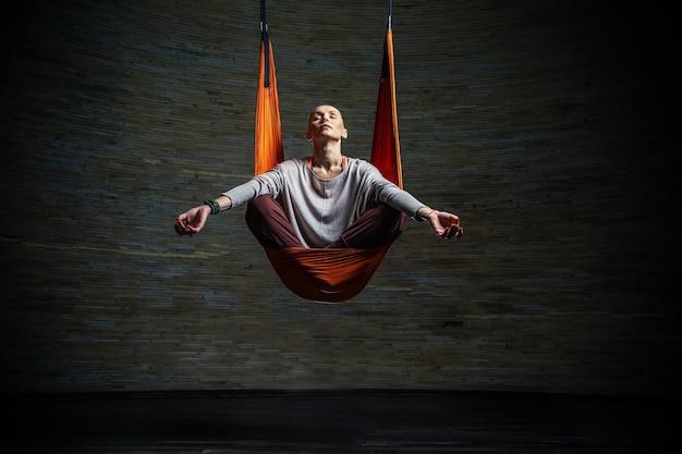 Longitud total de pacífica dama sentada en posición de loto con los ojos cerrados mientras practica yoga aéreo en una hamaca de color naranja brillante