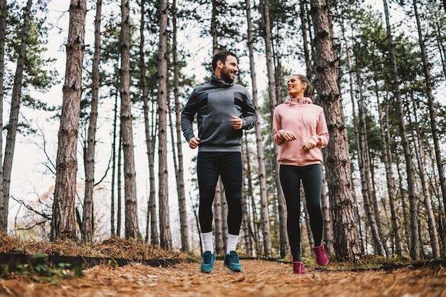 Longitud total de pareja en forma corriendo a través de bosques en otoño y preparándose para el maratón.