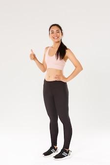 Longitud total de sonriente satisfecha, linda chica asiática de fitness, deportista en ropa activa mostrando el pulgar hacia arriba y sonriendo complacida, orgullosa athelte femenino ganar objetivo de entrenamiento diario, fondo blanco.