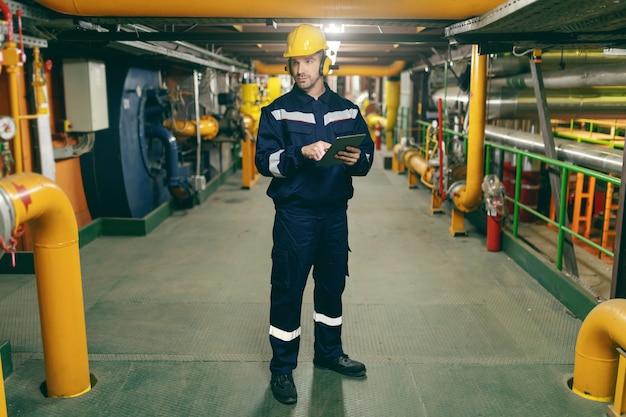 Longitud total del trabajador caucásico en traje protector, casco y antifonos en las orejas con tableta para el trabajo mientras está de pie en la planta de la industria pesada