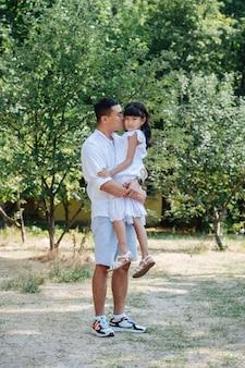 Longshot de un padre asiático sosteniendo a su hija en sus manos, besándola en la mejilla. ella está mirando a la cámara. están pasando tiempo en un parque, disfrutando de los últimos días cálidos de principios del otoño.