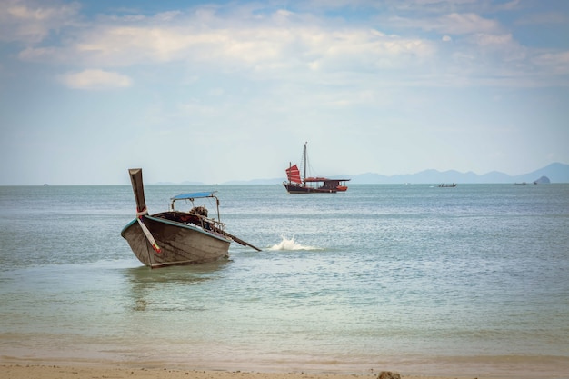 Longtail boat tailandés en la playa de phra nang ir al mar velero negro con velas rojas
