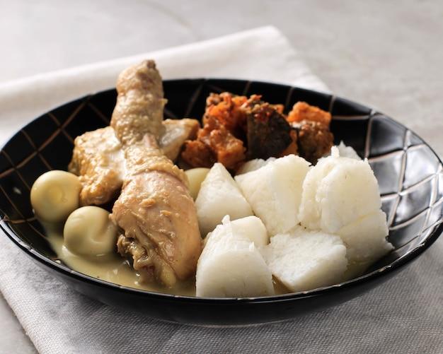 Lontong opor curry blanco indonesio con muslo de pollo y huevos de codorniz pollo y huevo duro