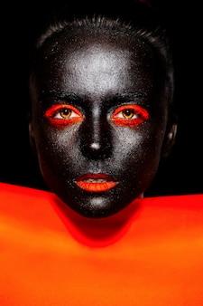 Look de alta costura. moda glamour hermosa mujer negra estadounidense con máscara negra con maquillaje naranja brillante y labios naranjas con material naranja