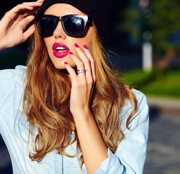Look de alta moda estilo de vida glamoroso modelo de mujer rubia en jeans casuales pantalones cortos de tela al aire libre en la calle con gorra negra en gafas