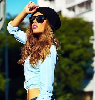 Look de alta moda estilo de vida glamoroso mujer rubia modelo chica en jeans casuales pantalones cortos de tela al aire libre en la calle con gorra negra en gafas