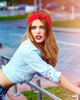 Look de alta moda estilo de vida glamoroso mujer rubia modelo chica en ropa casual al aire libre en la calle con pañuelo rojo