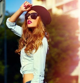 Look de alta moda estilo de vida glamoroso mujer rubia modelo de niña en jeans casuales pantalones cortos de tela al aire libre en la calle con gorra negra en gafas