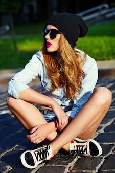 Look de alta moda estilo de vida glamoroso mujer rubia modelo de niña en jeans casuales pantalones cortos de tela sentado al aire libre en la calle con gorra negra en gafas