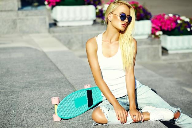 Look de alta moda glamour elegante sexy hermosa joven rubia modelo chica en verano brillante ropa casual casual con patineta sentado en la calle