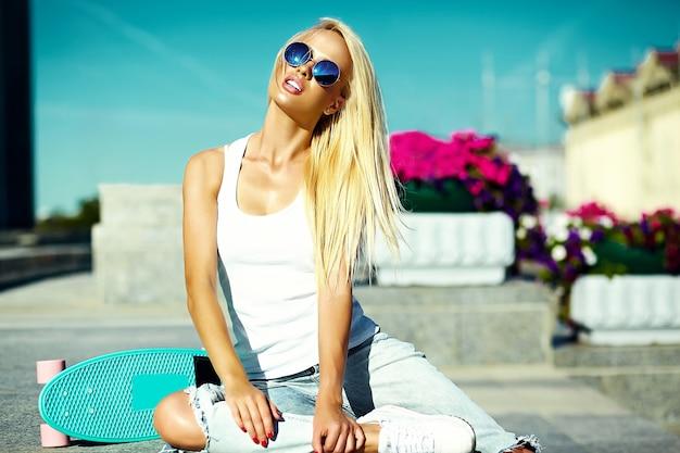 Look de alta moda glamour elegante sexy hermosa joven rubia modelo chica en verano brillante ropa casual hipster con patineta detrás del cielo azul en la calle