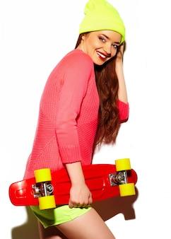 Look de alta moda glamour elegante sexy hermosa morena joven modelo en tela brillante hipster de verano en gorro amarillo con patineta