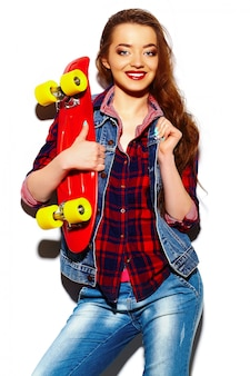 Look de alta moda glamour elegante sexy hermosa morena joven modelo en tela brillante hipster de verano con patineta