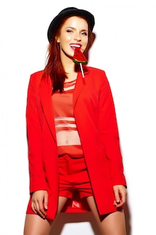 Look de alta moda glamour elegante sexy sonriendo gracioso hermosa joven modelo en tela de hipster casual rojo brillante de verano con dulce piruleta