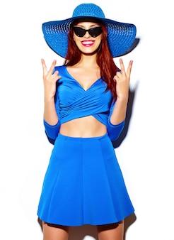 Look de alta moda glamour elegante sexy sonriendo gracioso hermosa joven modelo en verano brillante azul casual hipster tela en sombrero para el sol
