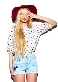 Look de alta moda glamour elegante sexy sonriente hermosa joven rubia modelo en verano brillante jeans hipster tela en sombrero rojo