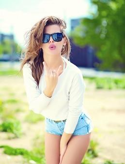 Look de alta moda glamour elegante sexy sonriente hermosa sensual joven modelo en tela brillante hipster de verano en pantalones cortos de jeans en la calle dando señal de rock and roll