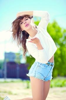 Look de alta moda glamour elegante sexy sonriente hermosa sensual joven modelo en verano brillante tela hipster en shorts de jeans en la calle dando beso