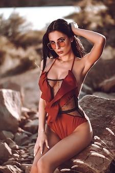 Look de alta moda glamour hermosa sexy elegante joven modelo perfecto bronceado piel limpia en traje de baño rojo.