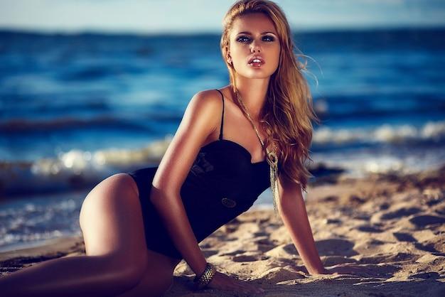 Look de alta moda glamour hermosa sexy elegante rubia caucásica joven modelo con maquillaje brillante, con perfecta piel limpia y bañada por el sol en traje de baño negro en la playa del mar en estilo de moda