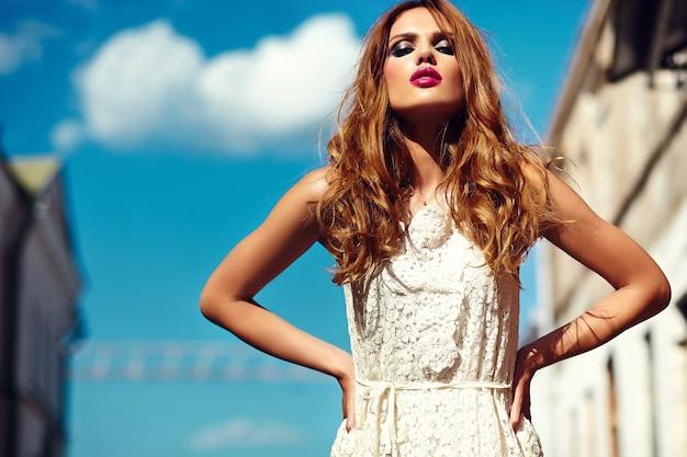 Look de alta moda glamour hermosa sexy elegante rubia joven modelo con maquillaje brillante y labios rosados con piel limpia perfecta en vestido blanco de verano en la ciudad detrás del cielo azul