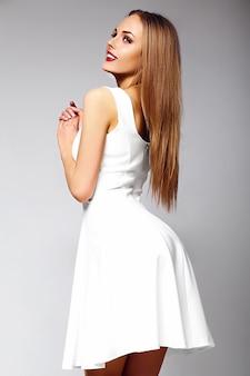 Look de alta moda glamour sexy elegante rubia sonriente joven modelo con maquillaje brillante con perfecta piel limpia y soleada en vestido blanco de verano con labios rojos