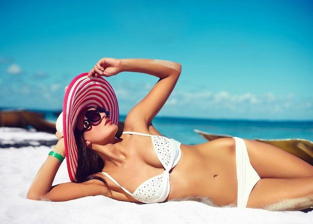Look de alta moda glamour sexy modelo de chica bronceada en bikini de lencería blanca en colorido sombrero de sol detrás de la playa azul del agua del océano