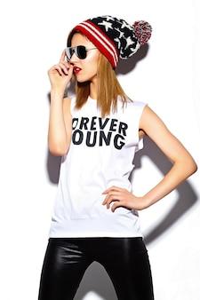 Look de alta moda modelo glamour elegante y bella mujer joven con labios rojos en tela hipster en gafas de sol en gorro colorido