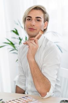 Look de maquillaje masculino sosteniendo un cepillo